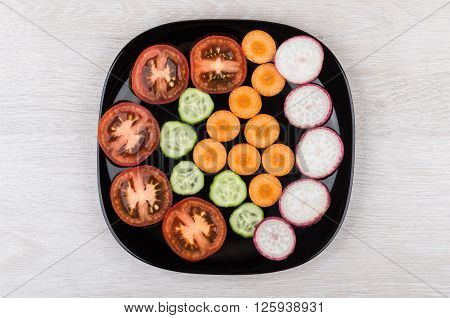 Slices Of Tomatoes, Radishes, Cucumbers And Carrots In Black Plate