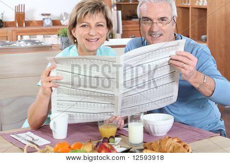 Senior couple reading newspaper