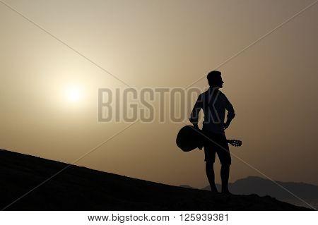 dark silhouette of guitarist and orbange sky at sunrise