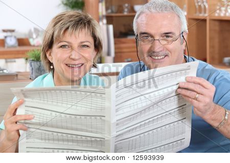 Senior couple reading newspaper