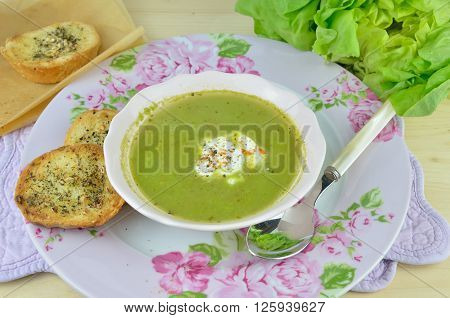 Bowl with fresh green vegetarian soup (pottage) with sour cream and pieces of garlic bread