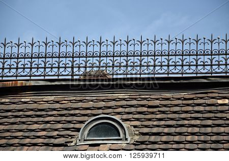 Old tiled roof with small oval window and ornamental iron construction on top