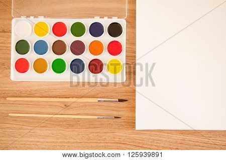Artist's workspace. Set of 18 watercolor paints in white base sheet of white watercolor paper 2 brushes on light woden background with copyspace. Artistic background.