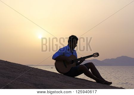 young man sitting on the beach playing guitar at sunrise
