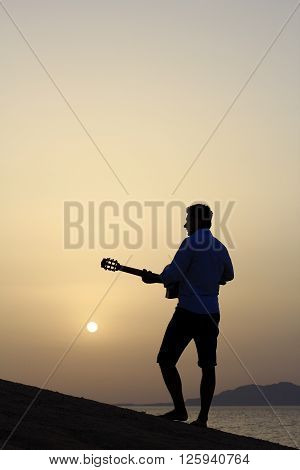 silhouette of a man guitarist performing on the beach at sunrise