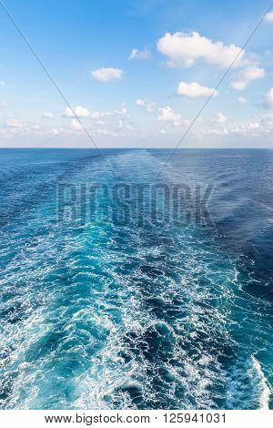 Wake of prop wash on blue ocean - vertical