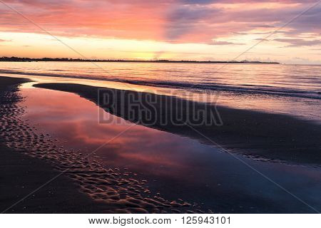 Pink sunset on the ocean beach. Fiji. Reflection of the sky in water. Puddles on the sand.
