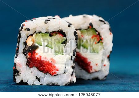 Pair of square sushi rolls with vegs cream cheese and red roe on blue background closeup