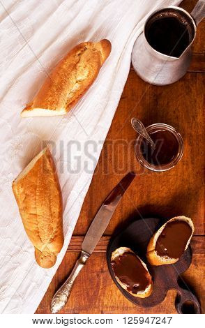 Breakfast appetizer with freshly baked French baguette, coffee and chocolate ganache on a table