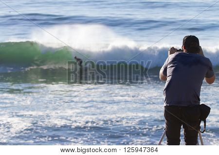 A man photographs a surfer from the shore