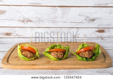 Bunless burger with bun replaces with lettuce leaves on wooden board