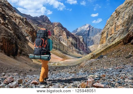 Girl with a big backpack is traveling in the Fan Mountains Tajikistan
