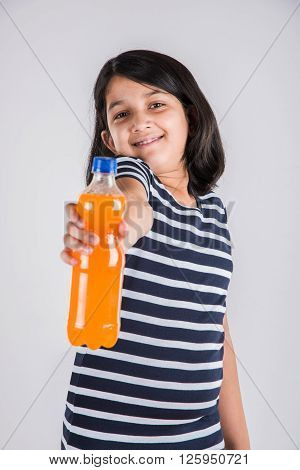 indian girl with cold drink bottle, asian girl drinking cold drink in pet bottle, girl kid and cold drink, indian cute girl drinking mango juice or orange juice in plastic bottle