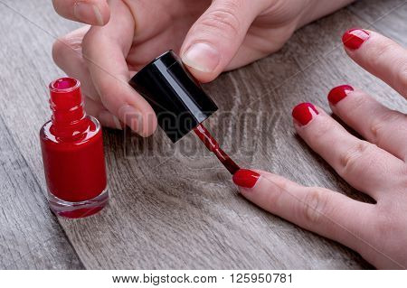 Close-up of female hands painting red nail varnish