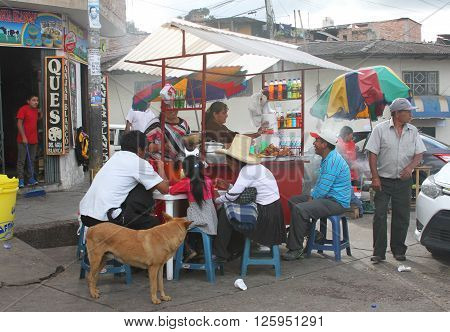 Cajamarca Peru - April 10 2016 - Peruvians eating at a small fried-chicken kiosk near a bus stop on a Sunday afternoon in Cajamarca Peru on April 10 2016