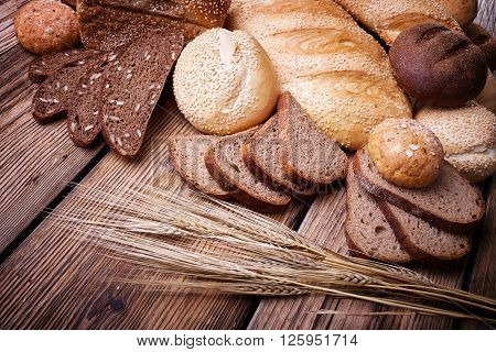 Fresh bread, sweet pastries, ears of ripe wheat, baked goods, harvest on the farm, great food, lots of baked goods, healthy food, a table of old wood, close-up bread, wood grain