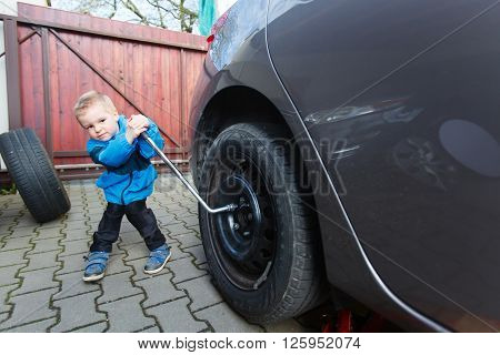 Boy Mounted Tires On A Car.