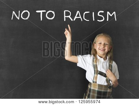 young sweet junior schoolgirl with blonde hair pointing with her finger to text no to racism written in classroom blackboard wearing school uniform in children education against racist behavior