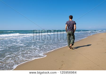 footprints of a man walking on the beach barefoot