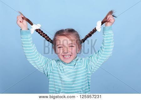 Laughing kid girl 3-4 year old having fun over blue. Wearing blue striped hoodie. Holding braids. Smiling baby.