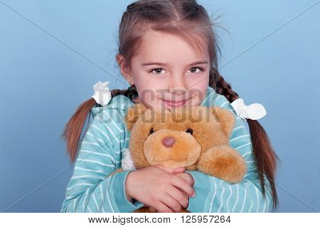 Smiling kid girl 3-4 year old playing with teddy bear over blue. Wearing blue striped hoodie.