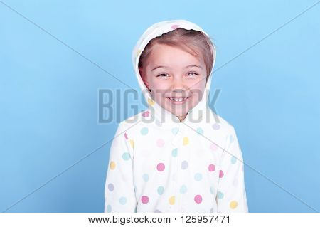 Laughing child girl 3-4 years old posing in room over blue. Wearing hoodie with polka dots. Looking at camera. Having fun.