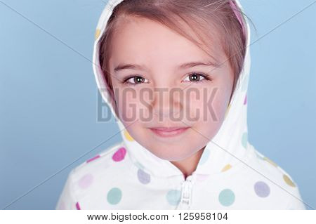 Cute baby girl 3-4 year old posing in room over blue. Wearing white hoodie with colorful polka dots. Looking at camera. Closeup portrait.