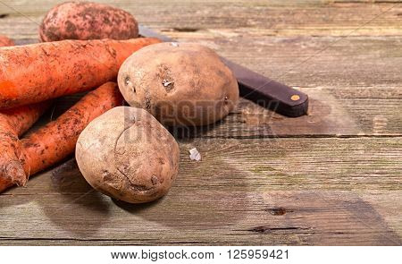 Vegetables the crude carrots and potatoes at the left against from gray boards. Nearby old knife. Close up small depth of sharpness