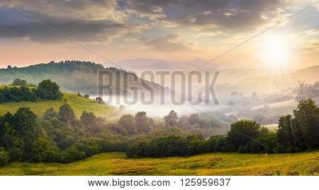 Fog On Hillside In Rural Area At Sunset