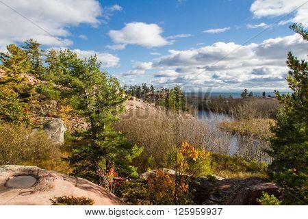 Autumn trees , red rocks and Chikanishing Creek in Killarney Provincial Park Ontario  Canada