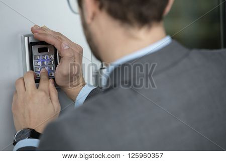 Close up of businessman hand pressing button on security system