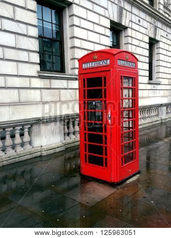 Vintage red phone cabine in London monumental item on a rainy day