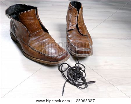 Pair of used shoes with shoelaces out and in front of them in a clew