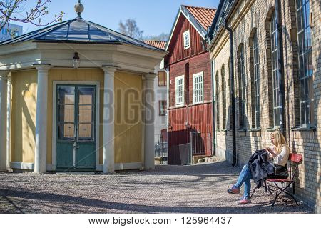 NORRKOPING, SWEDEN - APRIL 19 2014: Young woman enjoys sunshine on April 19, 2014 in the industrial landscape of Norrkoping. The historic industrial landscape has become a major tourist attraction.