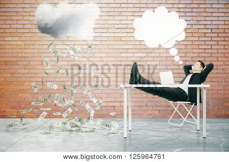Financial growth concept with speech bubble and businessman sitting at table with feet up looking at abstract money rain in red brick interior. 3D Rendering