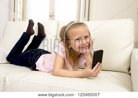 sweet cute and beautiful 6 or 7 years blond old female child in school uniform lying on home sofa couch using internet app on mobile phone playing online game looking happy and relaxed