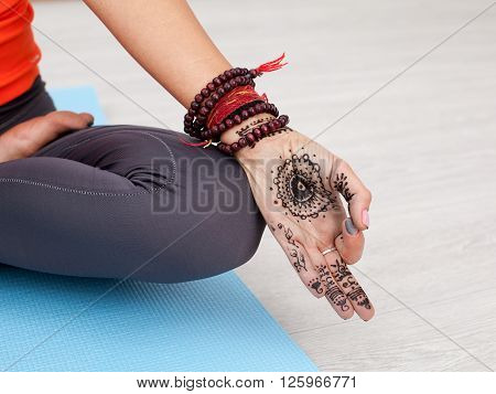 Lifestyle meditation and yoga concept. Close up female hand with mandala performing a mudra - thumb and forefinger are joined