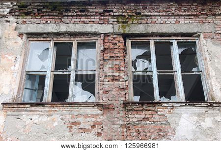 Two broken windows in an old abandoned building