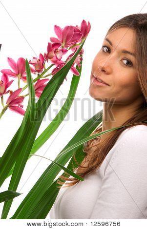 Brunette Woman Smelling Purple Orchid Flower