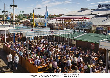 MUNICH, GERMANY - OCTOBER 02, 2015: The beer garden of the Braeurosl beer tent with the funfair area in the background