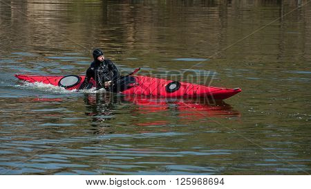 A Man In A Diving Suit Makes A Coup By Kayak