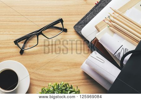 Topview of wooden desk with glasses coffee pencils and other items