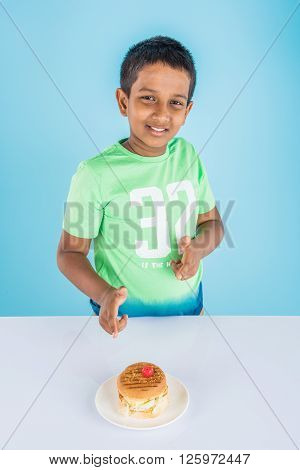 cute indian boy staring at burger served in white ceramic plate on white table , small asian boy and burger, over blue background