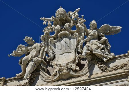 Emblem of Pope Clement XII among angels with trumpets at the top of Trevi Fountain in Rome