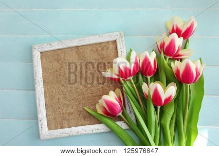Bouquet of variegated tulips with frame on blue wooden background