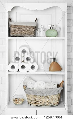 Bathroom set with towels, dispensers and basket on a shelf in light interior