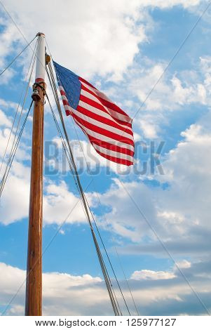 American Flag on a Sailboat Mast with Clouds and Sky in the Background