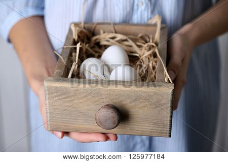 Eggs in basket in women hands on wooden background