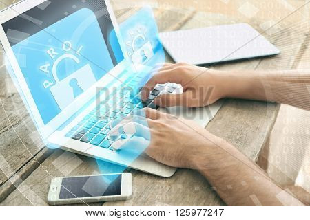 Man working on laptop with icons security on virtual display. Technology, internet and networking concept.