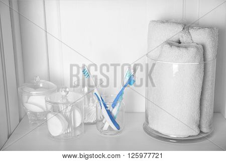 Bathroom set with towels, toothbrushes and sponges on a light shelf